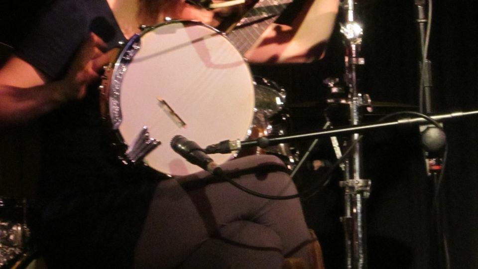 Rachael Marie singing into banjo.