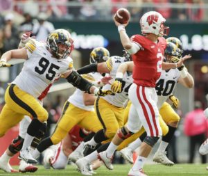 Drew Ott (95) tries to tackle Wisconsin quarterback Joel Stave (2) (Photo: www.thegazette.com).