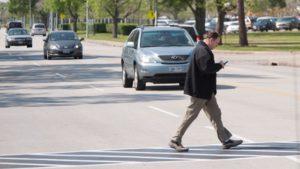 guy walking across street not looking at cars