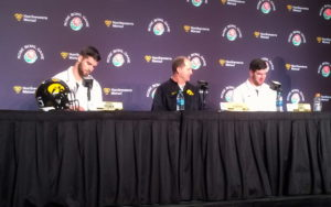 Phil Parker at the media podium with two linebackers--Fisher and Jewell--on either side of him.