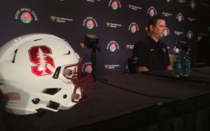 Stanford helmet in the foreground, with Mike Bloomgren at the podium to the right of the helmet