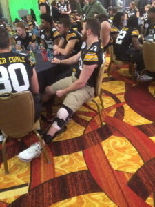 Jake Duzey sitting with a knee brace on his left knee
