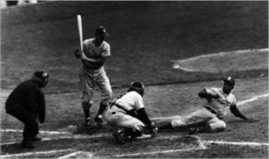 Jackie Robinson slides home beneath Yogi Berra's tag