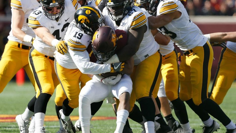 Iowa wraps up the Minnesota ball carrier (STEPHEN MALLY/ THE GAZETTE)