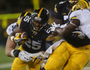 Running back Akrum Wadley (25) fights for extra yards in Iowa's 14-13 win over Michigan (via The Daily Iowan, Margaret Kispert, Alex Kroeze).
